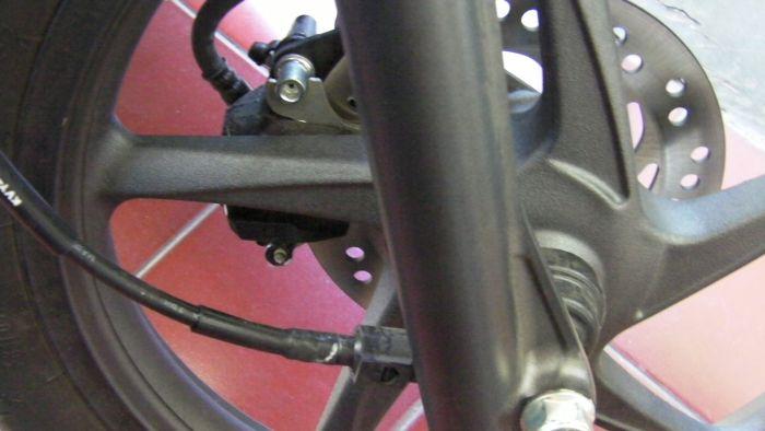 Velg racing dan rem cakram di kiri, kabel spedo di kanan